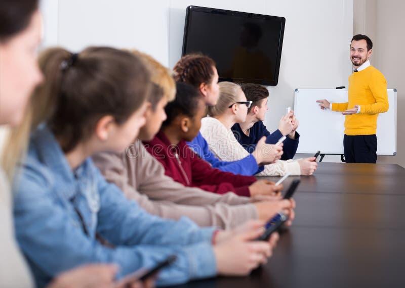Leerlingen die met rente teacher's lezing luisteren stock afbeelding