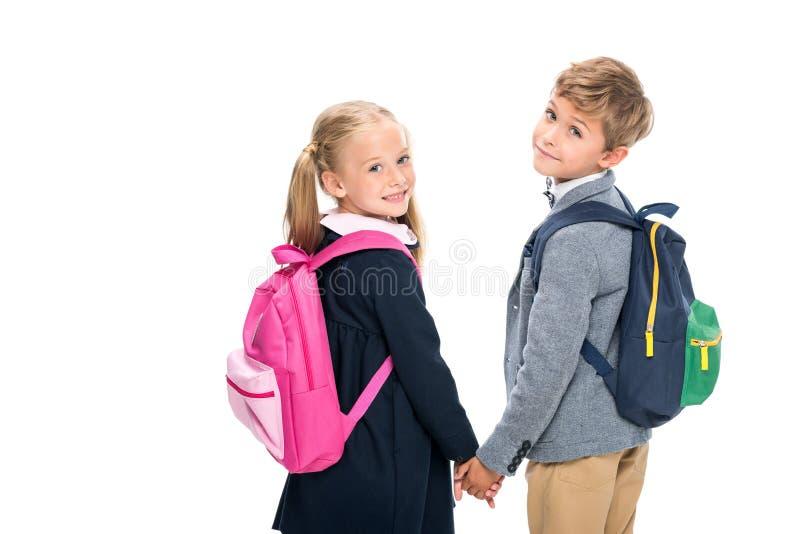 Leerlingen die met rugzakken terug kijken stock fotografie