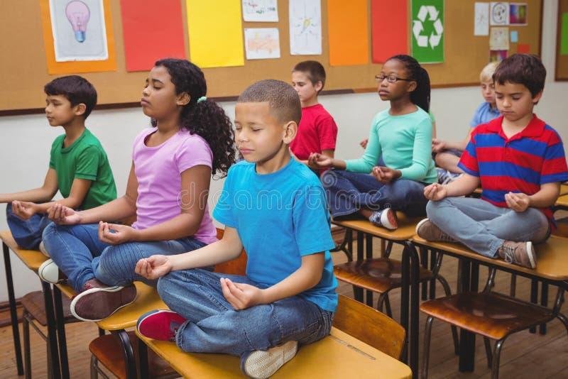 Leerlingen die op klaslokaalbureaus mediteren royalty-vrije stock foto