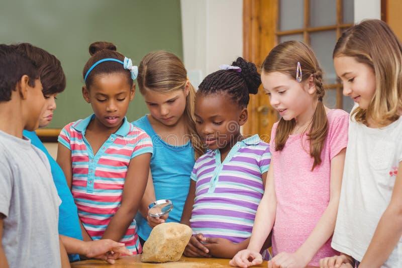 Leerlingen die rots met vergrootglas bekijken royalty-vrije stock fotografie