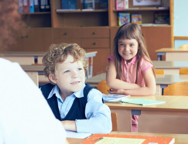 Leerlingen en leraar in klaslokaal in de basisschool Begin van het schooljaar stock foto's