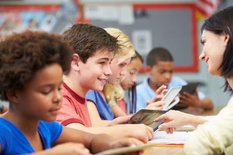 Leerlingen in Klasse die Digitale Tablet met Leraar gebruiken stock foto