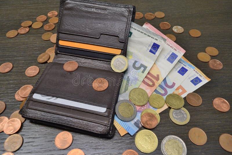 Leerportefeuille met diverse euro bankbiljetten en muntstukken stock foto's