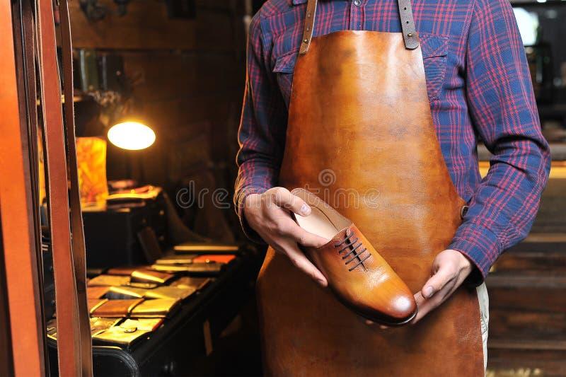 Leerschoenen in de handen van de meester stock foto's
