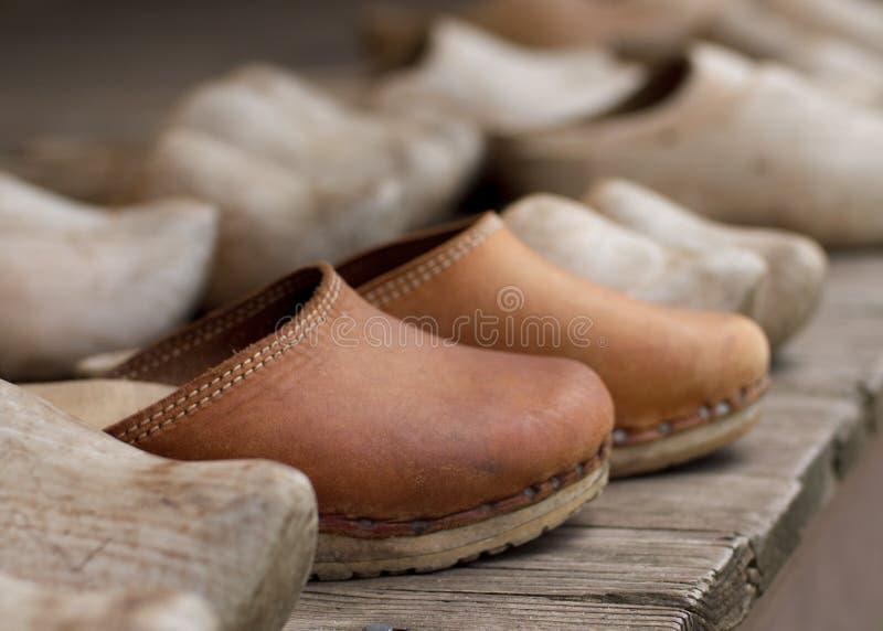 Leerschoenen onder diverse houten schoenen op een houten dek stock foto