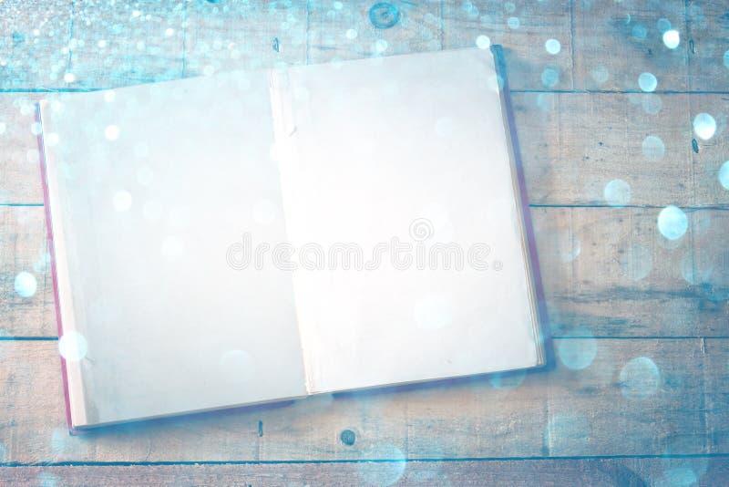 Leerseiten des offenen Buches über hölzerner Tabelle. Querprozeßeffekt, stockfotos