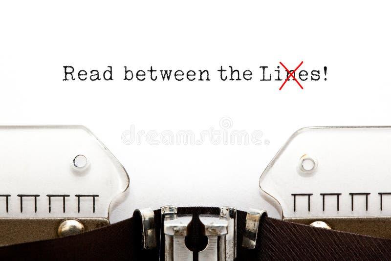 Lees tussen het Leugensconcept op Schrijfmachine stock afbeeldingen