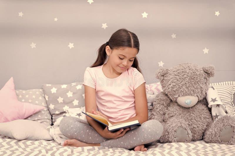 Lees v??r slaap Het meisjeskind zit bed met teddybeer gelezen boek Het jonge geitje treft naar bed te gaan voorbereidingen Pretti stock foto's