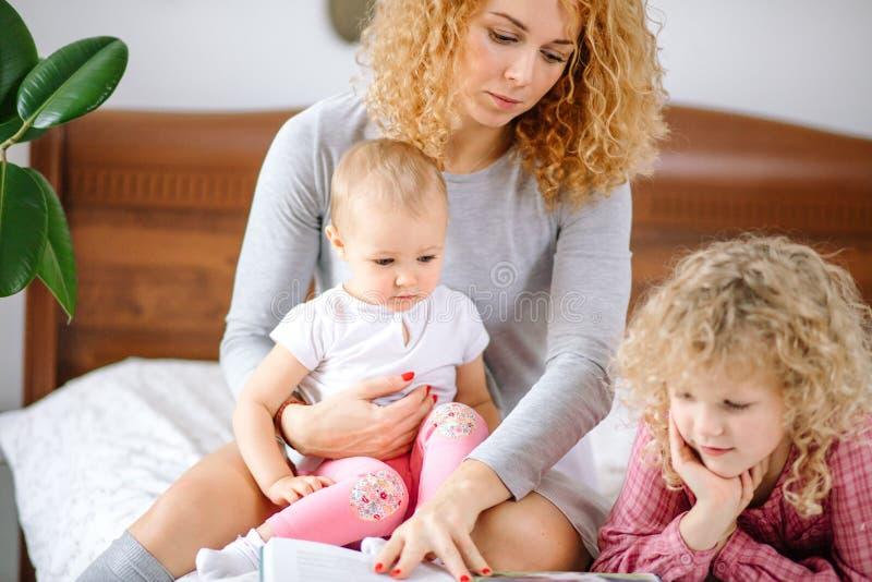 Leest de gember prettige vrouw gedichten aan haar kinderen stock foto