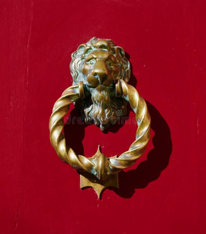 Leeuw gevormd deurhandvat op rode deur stock foto