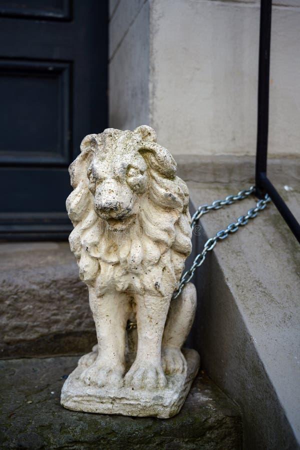 Leeuwbeeldhouwwerk dat van steen of gips wordt gemaakt dat voor een huisingang wordt geketend in de oude stad van luebeck, Duitsl royalty-vrije stock afbeeldingen
