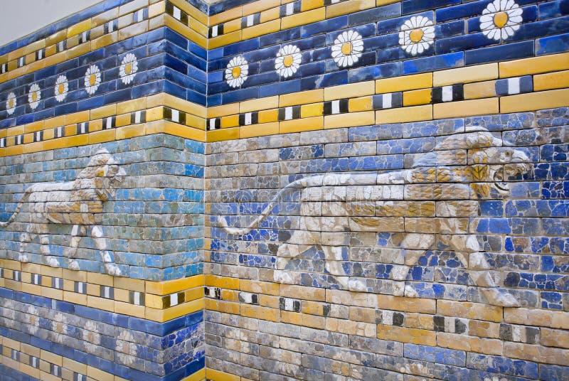 Leeuwen die op de jacht, gevormde muur volgen van de historische stad van Babylon royalty-vrije stock foto's