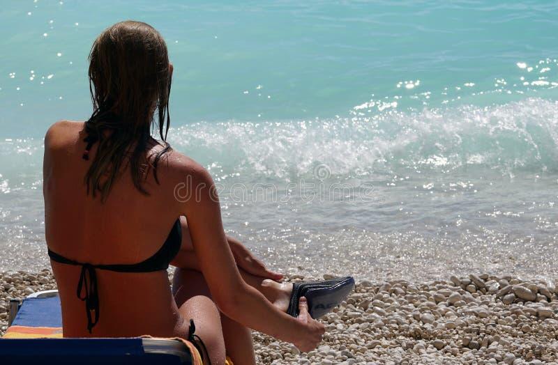 Lefkada, Greece, 16 July 2018, A beautiful woman admires the turquoise sea of Porto Katsiki, Lefkas. Healthy, skin, sexy, wind, smile, happy, sun, white royalty free stock photo