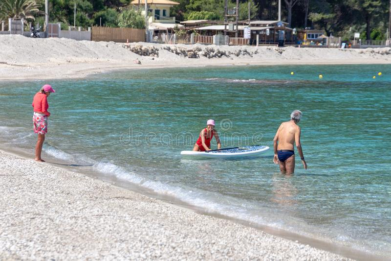 Seniors enjoying beach based leisure activities in the sea off Agios Ioannis beach, Lefkada, Greece. LEFKADA, GREECE - MAY 29 2018: Seniors enjoying beach based royalty free stock image