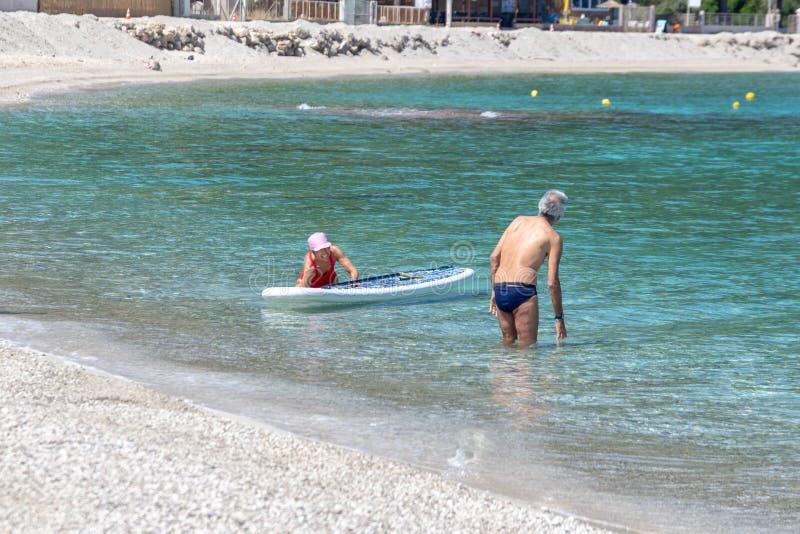 Seniors enjoying beach based leisure activities in the sea off Agios Ioannis beach, Lefkada, Greece. LEFKADA, GREECE - MAY 29 2018: Seniors enjoying beach based royalty free stock photo