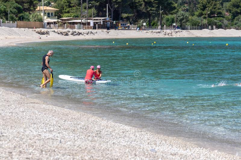 Seniors enjoying beach based leisure activities in the sea off Agios Ioannis beach, Lefkada, Greece. LEFKADA, GREECE - MAY 29 2018: Seniors enjoying beach based stock images