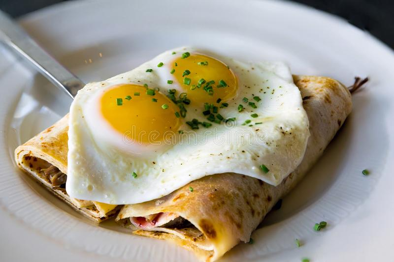 Lefse Norwegian Potato Crepes with Eggs Dish. Lefse Norwegian Potato Crepes with baked sunnyside eggs chives breakfast dish royalty free stock photo
