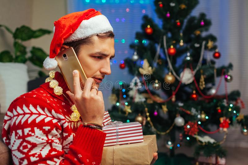 Left alone for Christmas. Sad man talking to friends on smartphone holding gift boxes. Celebrating New year at home stock images