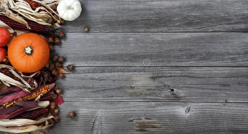 Left border of seasonal Autumn decorations on aged wood for the holiday background setting. Pumpkin, gourd, leaves, corn and acorns on left border of weathered stock photos