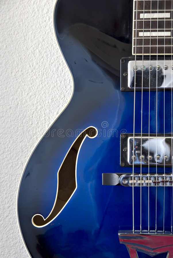 Left Detail of Jazz Guitar. Left side detail of blue jazz guitar with strings and f-hole stock photography
