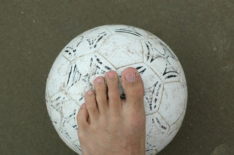 Left foot above the ball. Left foot above a beach soccer ball royalty free stock images