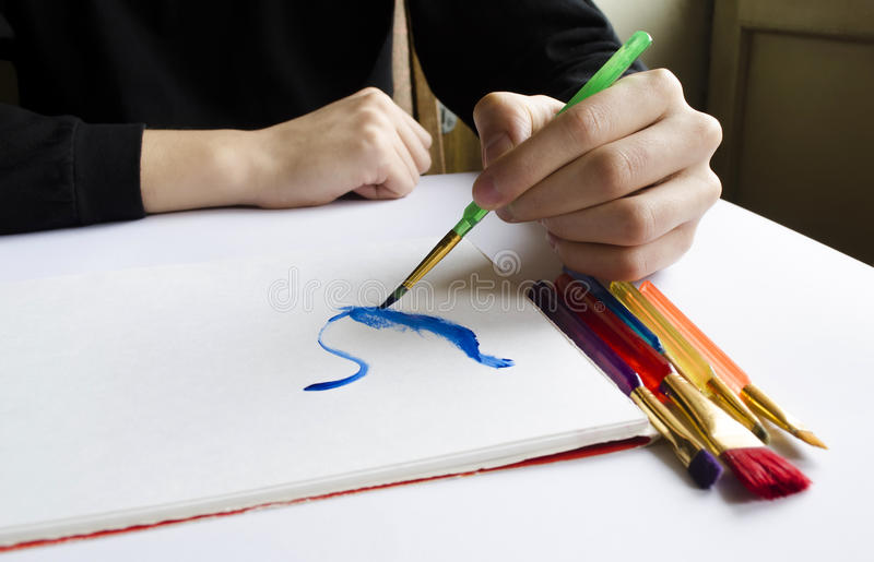 Left hand draws brush with blue paint on paper in album with sev. The left hand draws a brush with blue paint on paper in an album with several colorful brushes stock image