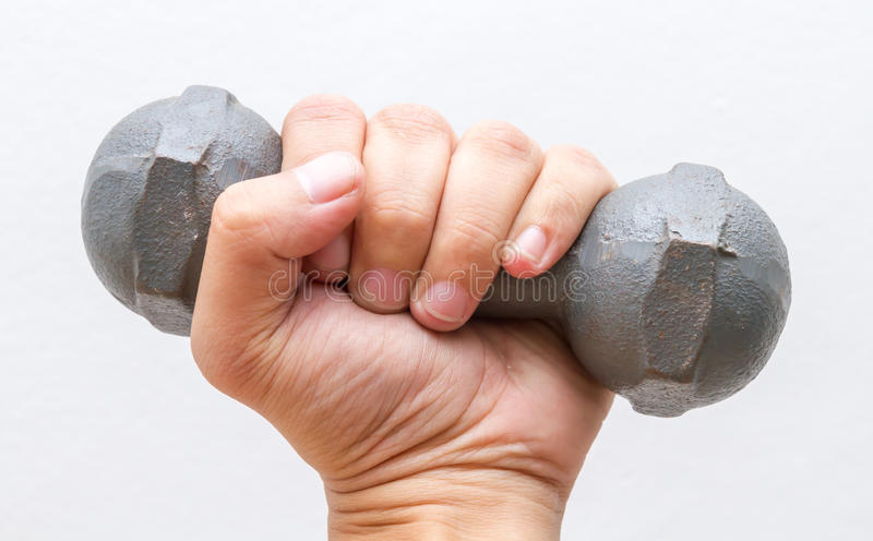 Left hand hold small dumbbell. Left hand hold small dumbbell on white wall background royalty free stock photo