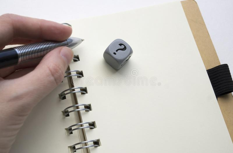 Left hand holding a pen above a blank page of a spiral bound notebook, gray dice with question mark on it stock photo