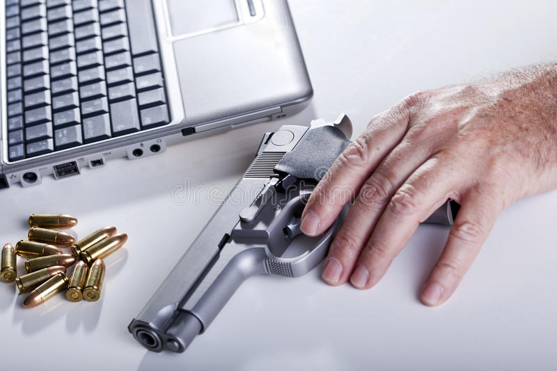 Computer Criminal. The left hand of a mature adult man resting on a 9mm handgun. 9mm bullets are scattered in the background as well as a laptop computer royalty free stock image