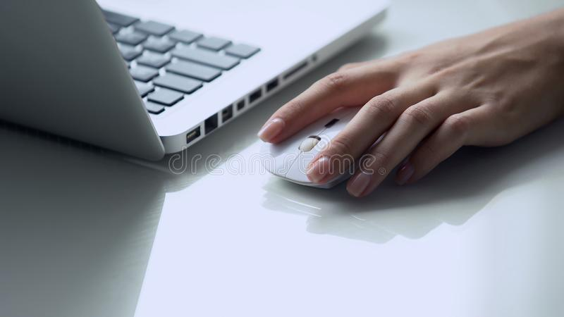 Left-handed female using wireless mouse with laptop, modern personal computer stock photography
