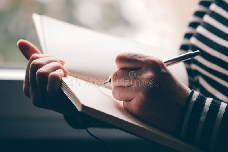 Left-handed woman writing diary royalty free stock photos