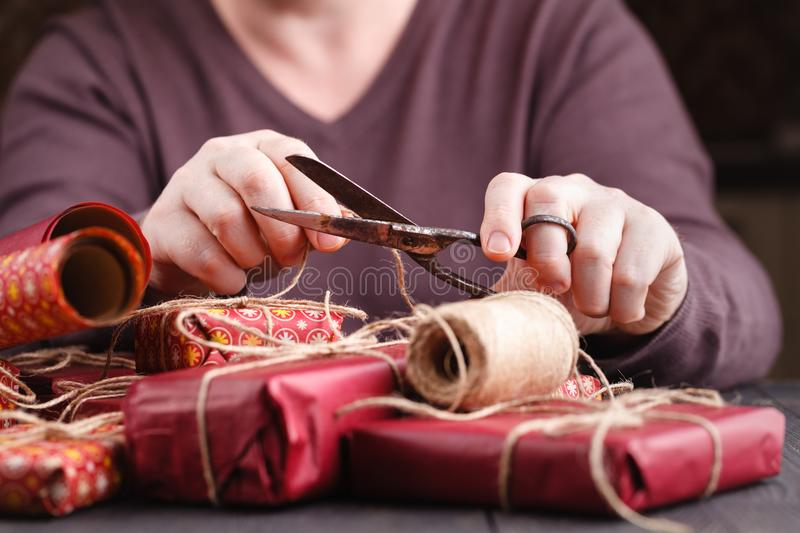 Left handled man cutting a wrapping ribbon on a christmas gift stock photo