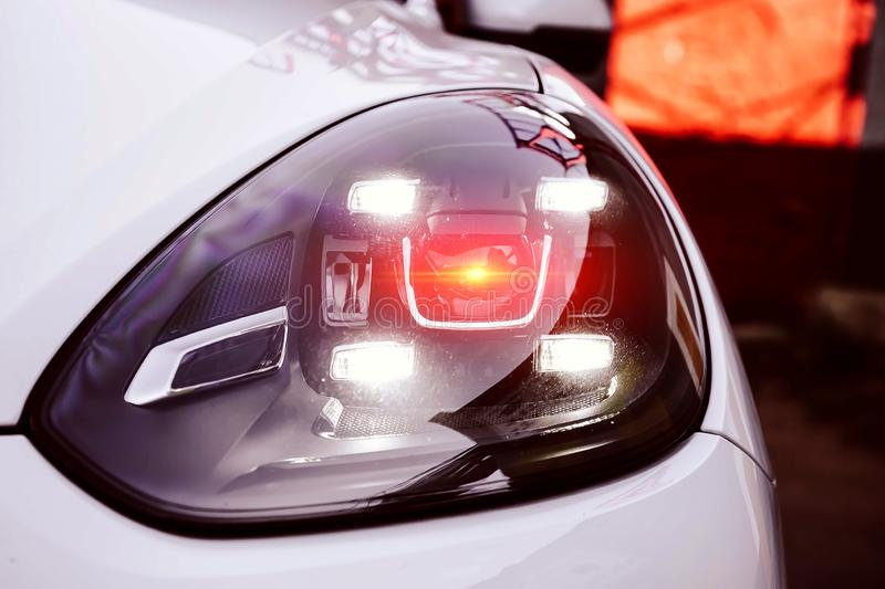 Left Led headlights of a white premium suv.  With red orange lighting from lens. New generation of car light. Closeup of a hood. And bumper automobile detail stock photo