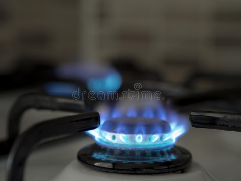 Left open oven gas in the home kitchen. close-up blue colored burning gas royalty free stock photos