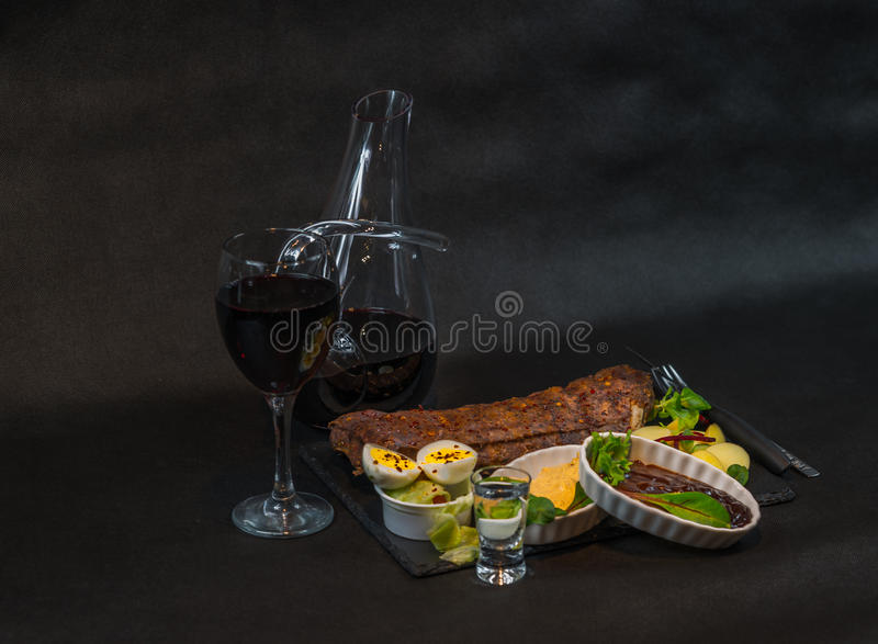 Left side view on a rack of pork ribs with potatoes, sauces, bread and red wine in a carafe and glass, the second glass of vodka. A delightful dinner royalty free stock images