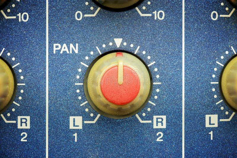 Left to right red pan knob. On a blue mixing table, close up view stock images