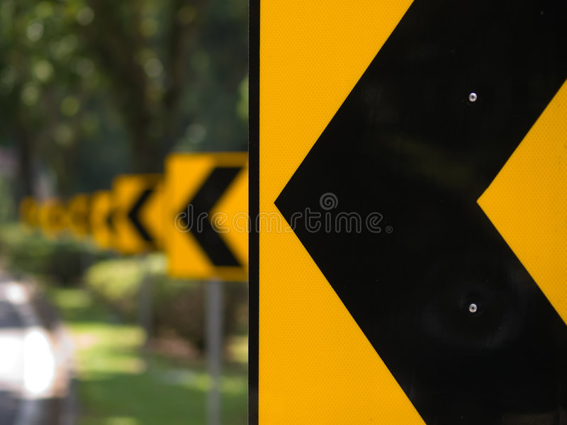 Left Turn. Arrows signs on a road along a bend royalty free stock image