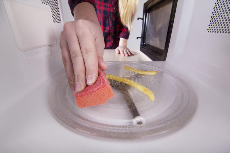 Leftover food in microwave. Hand with sponge cleaning oven royalty free stock images