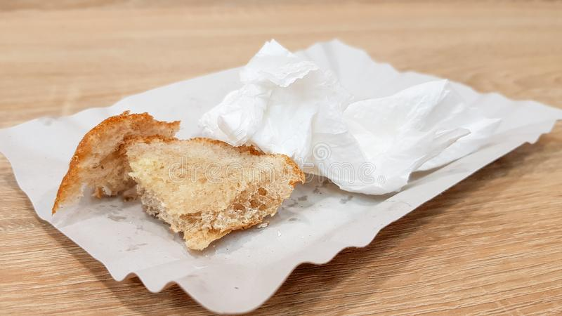 Leftover food on a paper plate and empty dirty paper coffee cup on a wooden table in a fast food cafe stock image
