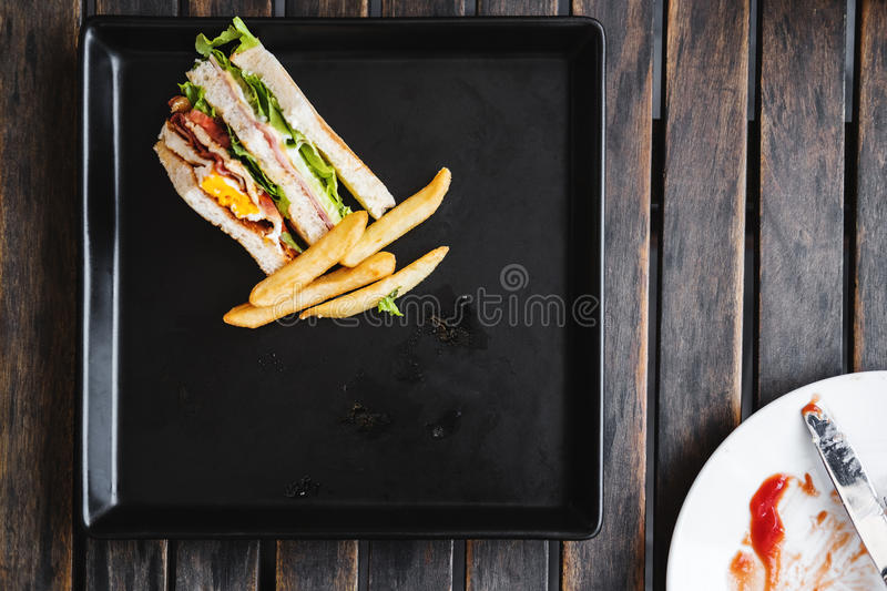 Leftover toasted club sandwich with french fries on black dish stock images