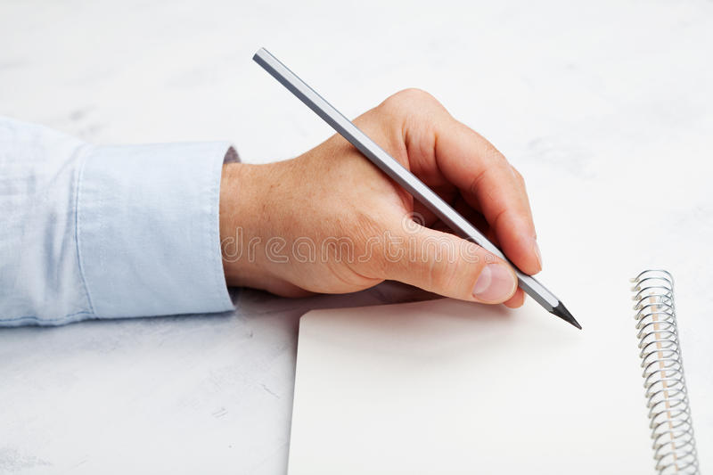 Lefty writes in empty notebook on white table. International Lefthanders Day. Lefty writes in empty notebook on table. International Lefthanders Day stock photography