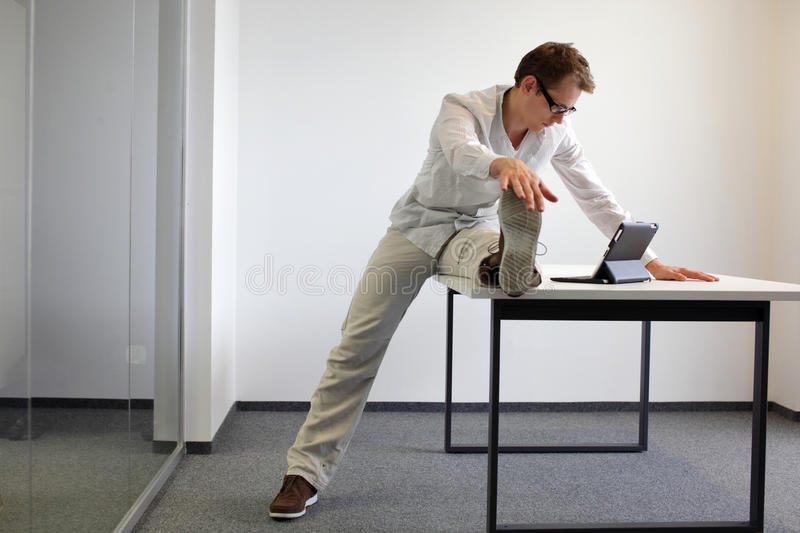 Leg exercise durrng office work royalty free stock image