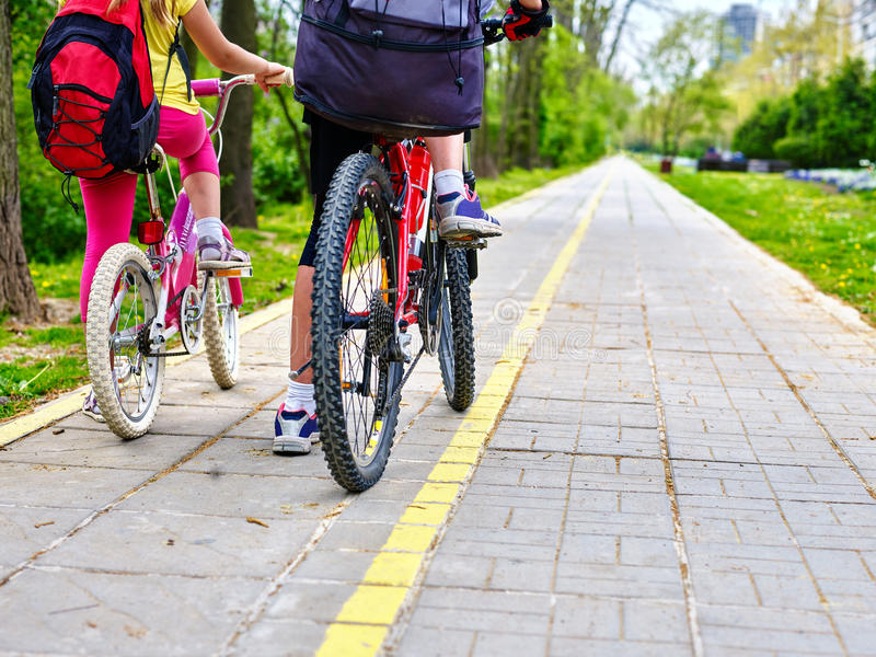 Leg of girls ride on bicycle. Bicycle girl. Legs of bicycle girl . Girls children cycling on yellow bike lane. Bike share program save money and time at city royalty free stock photography