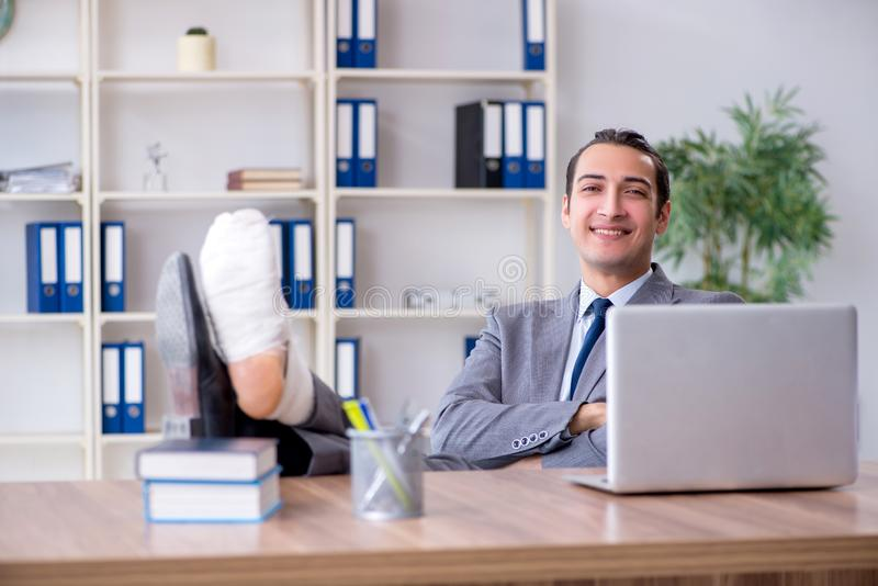 Leg injured male employee in the office royalty free stock images