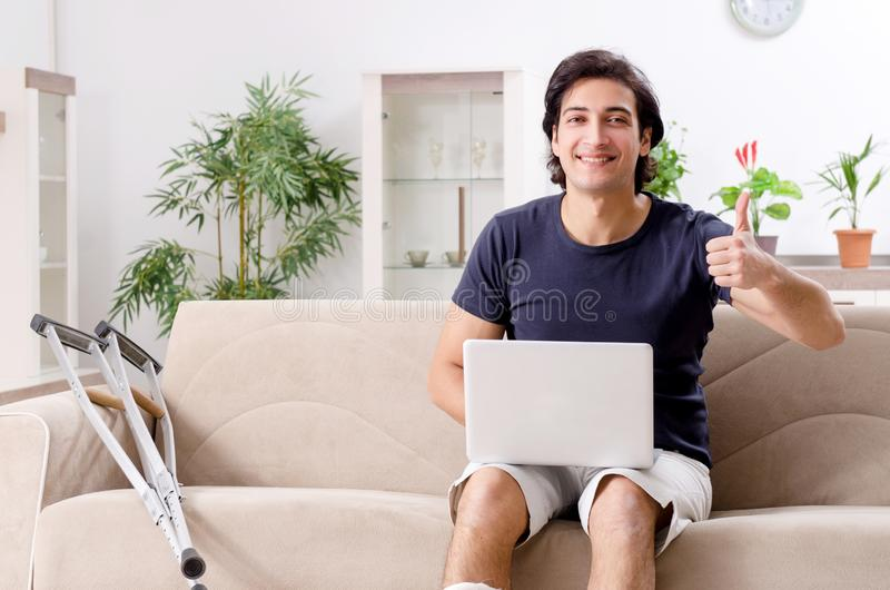 Leg injured young man suffering at home stock images