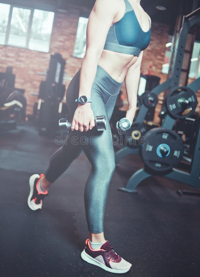 Leg muscle training, lunges with dumbbells. Athletic model woman with sports body exercising with dumbbells in the gym. Training concept stock photos