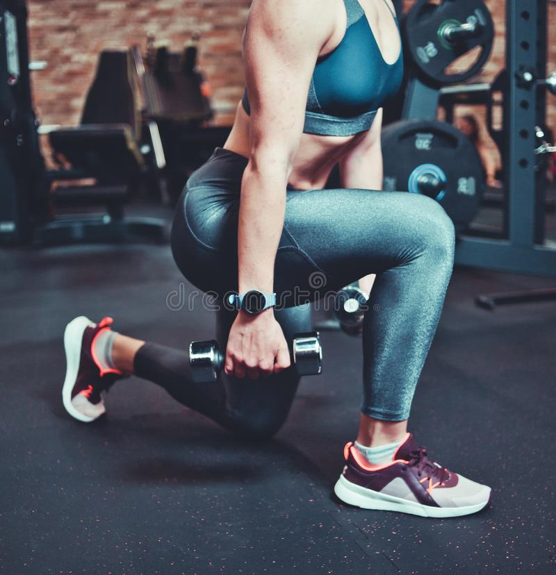 Leg muscle training, lunges with dumbbells. Athletic model woman with sports body exercising with dumbbells in the gym. royalty free stock photos