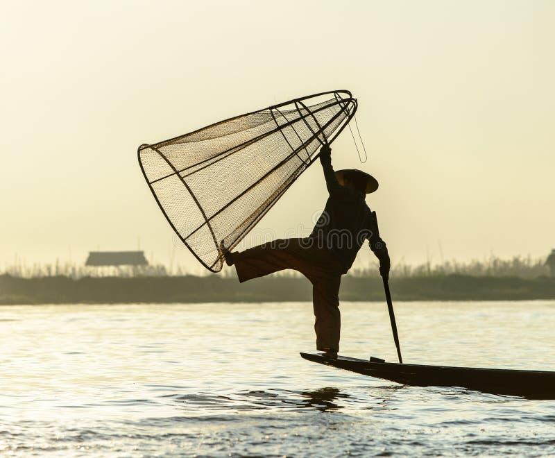 Leg rowing fisherman at Ine Lake. Burmese fisherman on bamboo boat catching fish in traditional way with handmade net. Inle lake, Myanmar (Burma royalty free stock photo