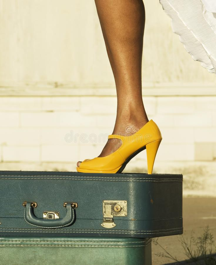 Leg and shoe on a suitcase stock photography