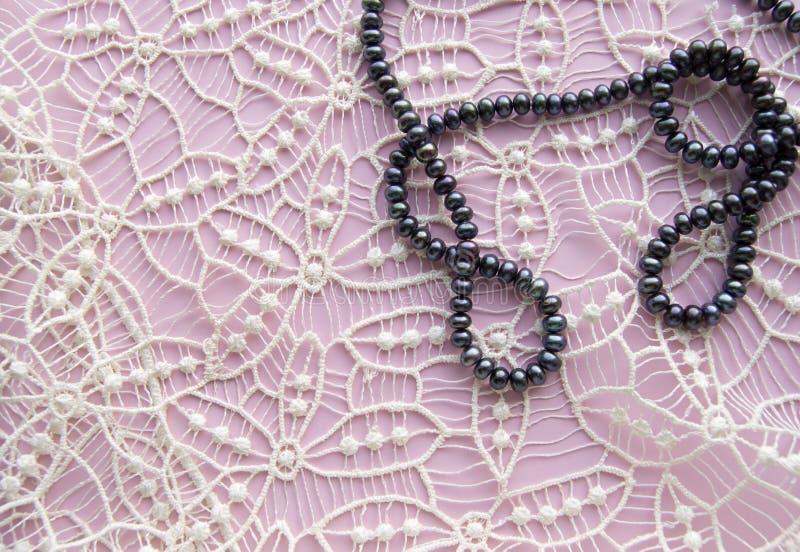 Leg Vlakke roze achtergrond en het schitterende kant, de schitterende halsband van zwarte parels, en de modieuze armband Schoonhe royalty-vrije stock afbeeldingen